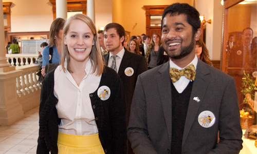Male and female students walking through the state capitol smiling